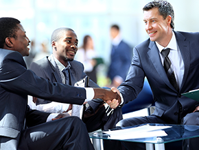 Three men in suits shaking hand and about to start meeting.